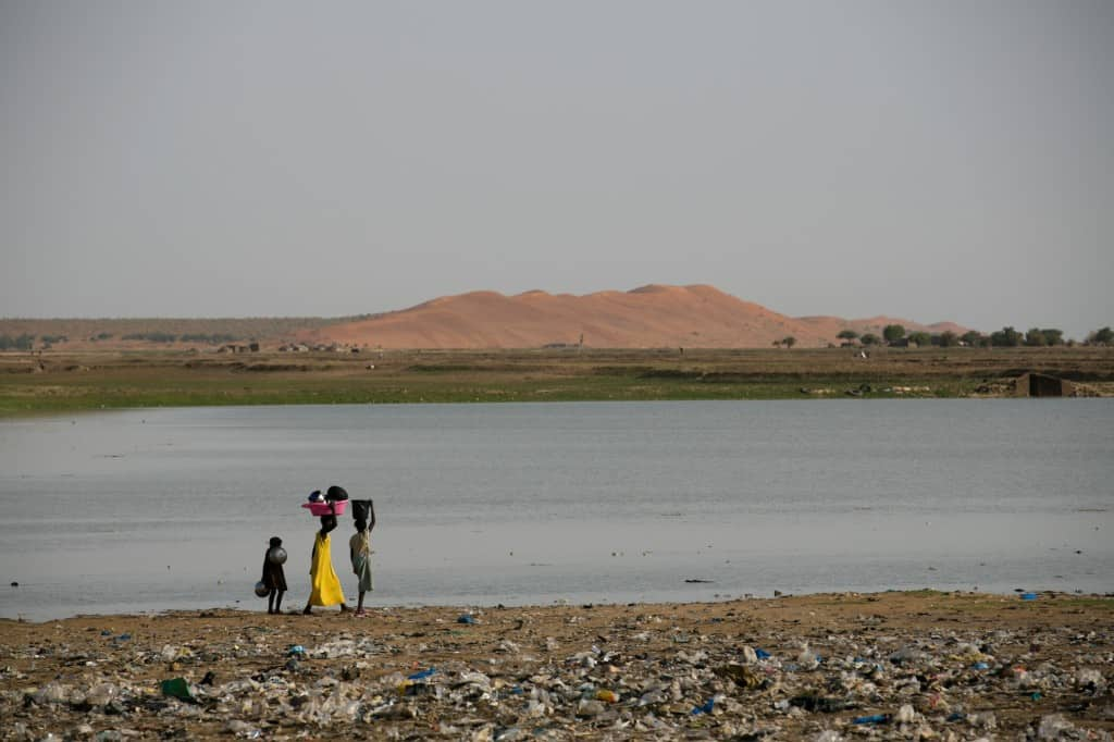 Three children walk to clean dishes in the Niger river in Gao, Mali.