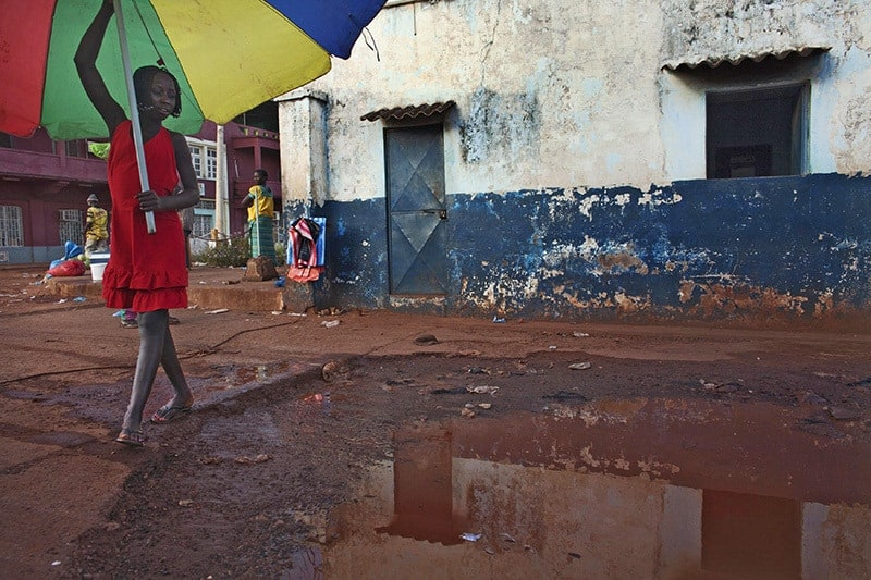 A girl holds an umbrella near the port in Guinea-Bissau's capital Bissau