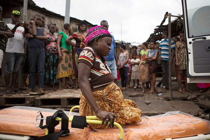 A pregnant woman sits herself down on a stretcher as people watch from a distance, afraid to touch her as she is suspected of having Ebola, in Freetown, Sierra Leone.