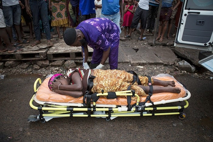 A pregnant woman lays by herself on a stretcher as people watch from a distance, afraid to touch her as she is suspected of having Ebola, in Freetown, Sierra Leone, 19 September 2014.