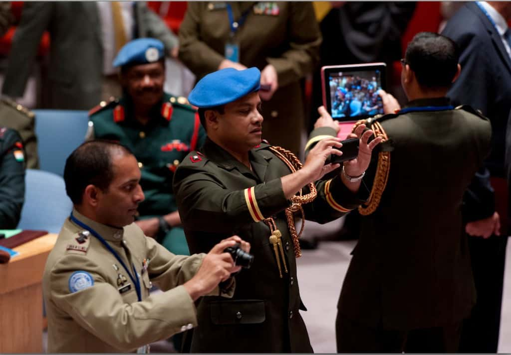 The Security Council received briefings from senior UN military officials, including the Military Advisor for Peacekeeping Operations and the Force Commanders of three UN peacekeeping missions. UN military officers attending the meeting take pictures in the Council Chamber. 09 October 2014