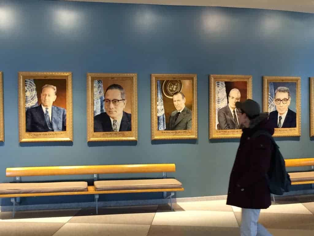 A woman who works at the United Nations and others refers to the wall of portraits in New York of secretaries-general