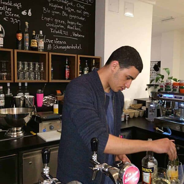 At the Magdas Hotel, located in the Prater neighborhood of Vienna, refugees who have won asylum status in Austria do paid work while learning new marketable skills. An Algerian employee, above, tending bar. DULCIE LEIMBACH