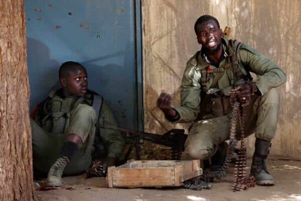 A Malian soldier gestures to his comrades during fighting with Islamists in Gao, February 21, 2013. French and Malian troops fought Islamists on the streets of Gao and a car bomb exploded in Kidal on Thursday, as fighting showed little sign of abating weeks before France plans to start withdrawing some forces. JOE PENNEY