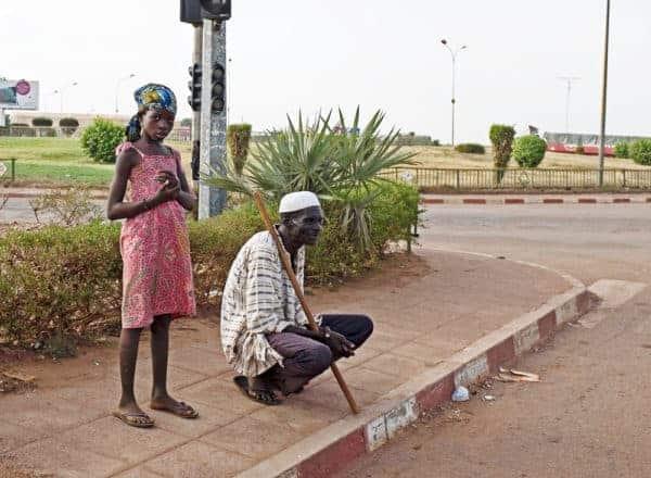 A girl street child helps a blind man, Ouagadougou. NABILA EL HADAD