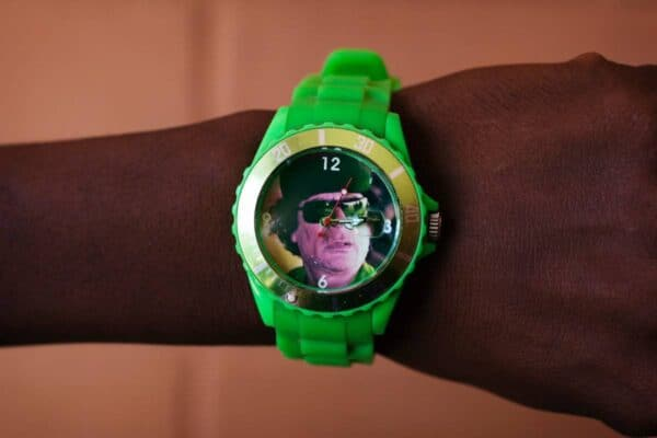 A man in Agadez, Niger, a desert outpost that has become a migrant way station to Libya, wears a watch bearing the face of Libya's former leader, Muammar Qaddafi. JOE PENNEY/REUTERS