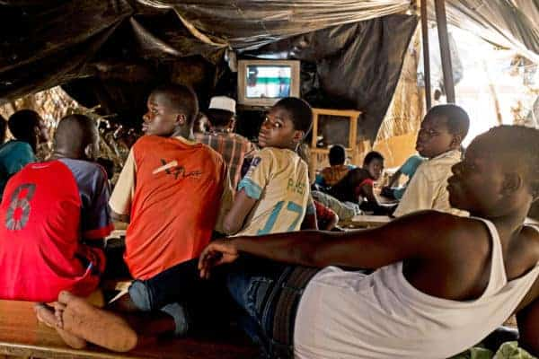 Street children with other people in a movie theatre built under a paillotte in Ouagadougou Burkina Faso