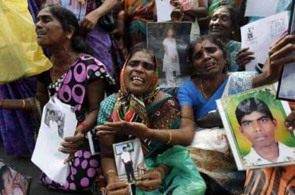 Tamil women with images of family members who disappeared during the Sri Lanka civil war at a protest in Jaffna, August 2013. REUTERS/Dinuka Liyanawatte/CREATIVE COMMONS